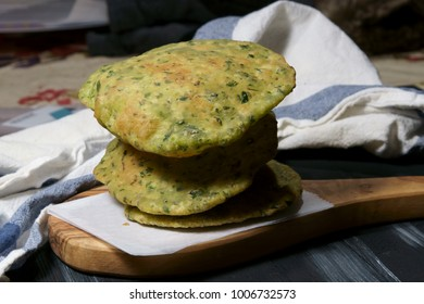 Green Palak Poori, an Indian fried puffed bread with chopped spinach leaves in whole wheat flour.
