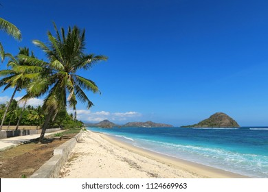 Green palm trees on white sand ocean beach with little mountains, Sumbawa island, Indonesia