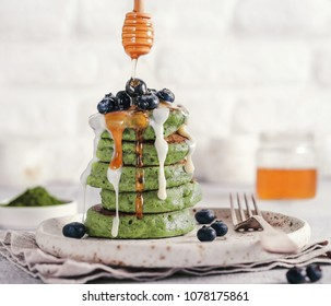 Green pancakes with matcha tea, dressed blueberries, white vanilla sauce or condensed milk and honey. Ideas and recipes for healthy breakfast with superfood ingredients.