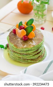Green pancakes with spinach and bananas decorated citrus, mint and cranberry