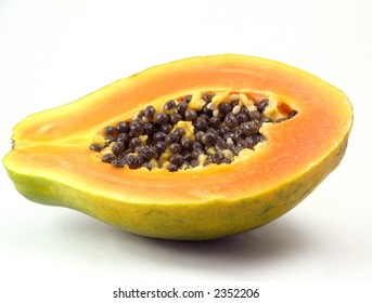 Green papaya with orange and yellow flesh and black seeds, cut in half on white background.