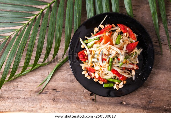 green papaya salad  in black plate on wooden background