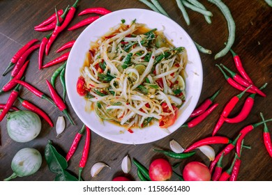 green papaya salad in white plate on wooden background,somtum in thailand,thai papaya salad with vegetables