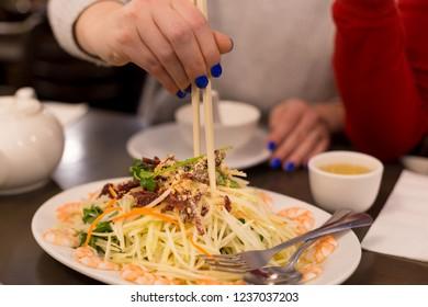 Green papaya salad with a woman's hand holding chopsticks.