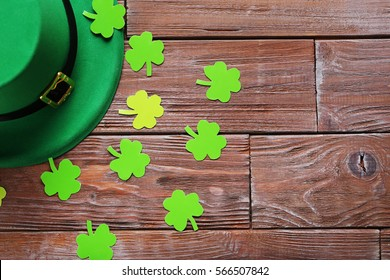 Green paper clover leafs and hat on a brown wooden table