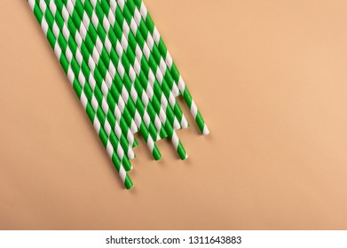 Green paper eco straws on apricot background