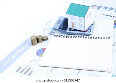 Green paper house on calculator with books  on business report chart for mortgage loans concept