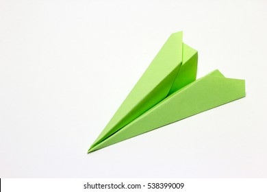Green paper plane on a white background.