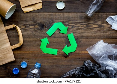 Green paper recycling sign among waste materials paper, plastic, polyethylene on dark wooden background top view