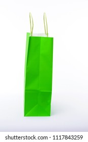 Green paper shopping bags on white background. Empty area.