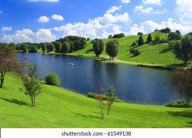 Green park with lake and blue sky in German