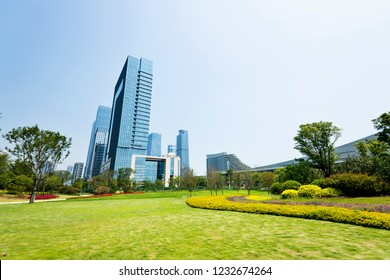 Green park next to business center buildings.