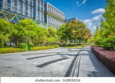Green park next to business center buildings detail. Healthy greenery with modern glass high rising skyscrapers and blue sky background. Abstract urban development and architecture wallpaper.
