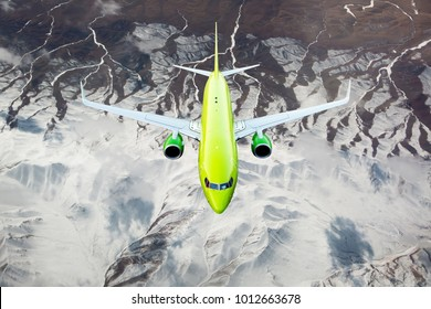 Green passenger plane flies over snow-capped mountain peaks