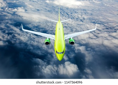 Green passenger plane fly over the clouds. View from above.