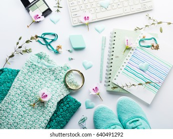 Green pastel mint color lifestyle woman clothes flat lay with accessories, notebook and keyboard