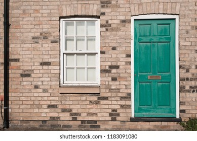 Green pastel vintage front door on a restored brick wall of a Georgian house residential building with white wooden sash window