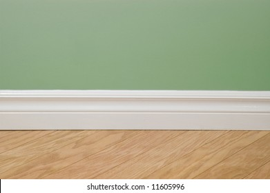 Green pastel wall, baseboard and hardwood flooring