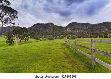 Green pasture field of a farm in rural NSW in Australia - agricultural site for steer growth with fences and mountain range in background