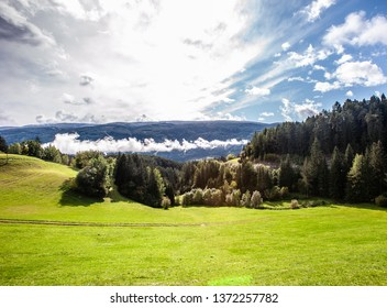 Green pasture lands in the Italian Alps. Change of weather. Dolomites, Sudtirol, Italy