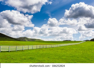 Green Pasture With White Fence With Large Puffy Clouds