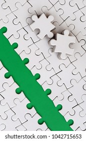 The green path is laid on the platform of a white folded jigsaw puzzle. The missing elements of the puzzle are stacked nearby. Texture image with space for text