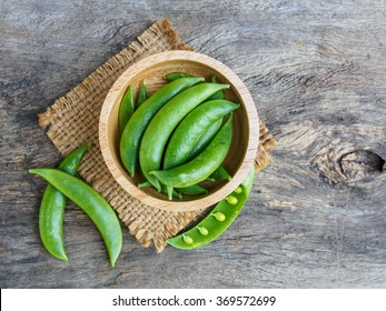 Green pea in bowl of top view on rustic wooden background with copy space