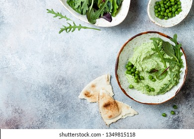 Green pea hummus spread or dip with mix salad leaves. Healthy raw summer appetizer, vegan, vegetarian snack. Copy space