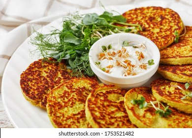 green pea and oatmeal pancakes on a white platter with plain greek yogurt sauce with fresh sprouts of pea and wheat, healthy diet concept, horizontal view from above