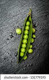 Green pea in the pod on dark slate