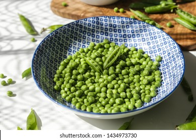 Green pea seeds in blue plate with pea pods on white background.