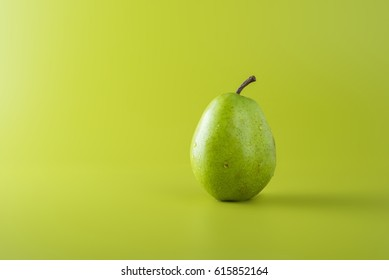 Green pear over green background, copy space