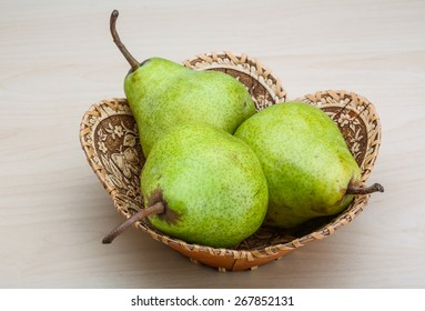 Green pears in the basket on wood background