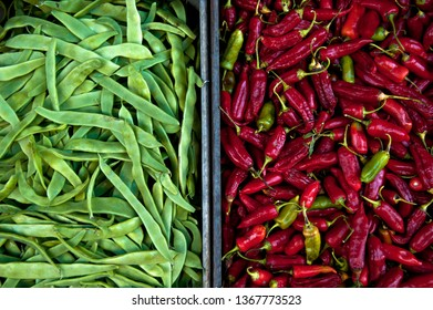 Green peas and chilli peppers in boxes on the street market