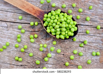 Green peas on wooden background and big spoon - vintage environment