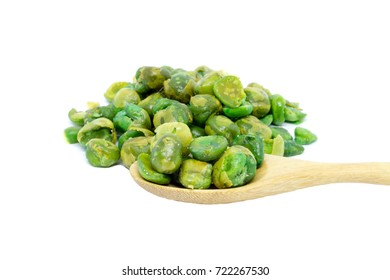 Green peas with salt and wooden spoon isolated on white background.