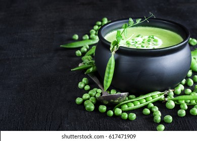 Green peas soup on dark wooden background. Low key photo. Copy space background.