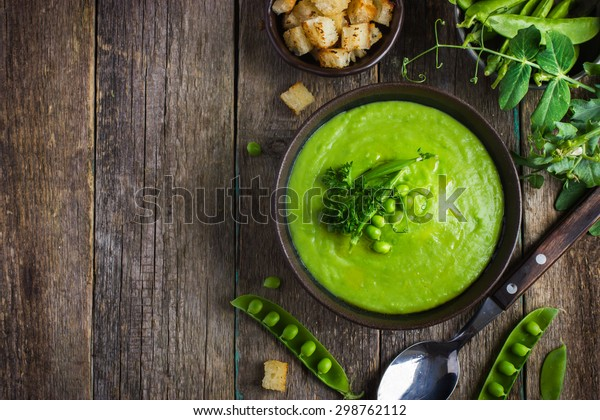 green peas soup on rustic background, top view, copy space