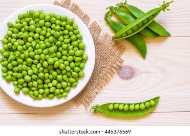 Green peas in white bowl on wooden background, top view or flat lay