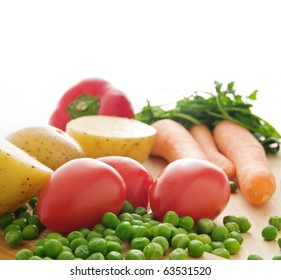 Green peas,tomatoes,potatoes,carrots,and a red pepper on a wooden plank - isolated on white background with copy space