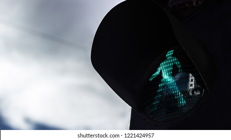 Green pedestrian light on dramatic sky