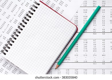 Green pencil and blank notebook on financial chart.Accounting concept.