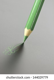 green pencil drawing a four-leaf clover, simple drawing and photo combination