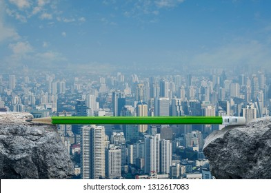 Green pencil on rock mountain over modern city tower, office building and skyscraper, Business success strategy plan concept