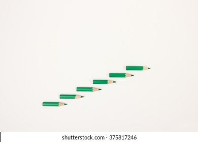 Green pencils forming steps upward - minimal image to visualize personal growth, career development, success