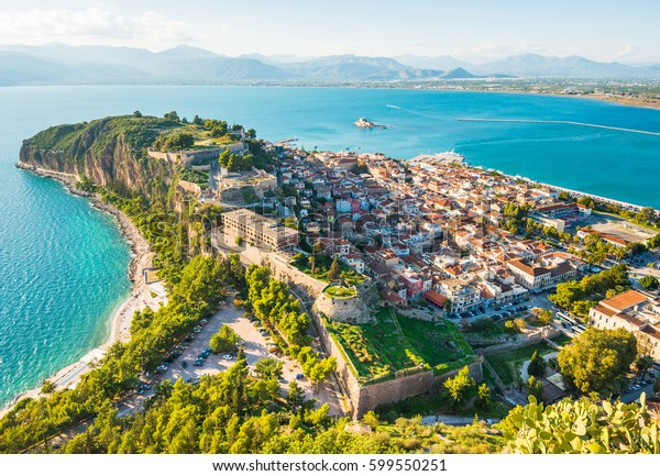 Green peninsula with Nafplion city in Greece from above with blue Mediterranean sea, old town roofs and small port