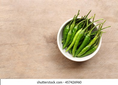 Green Pepper in a bowl on wooden table background