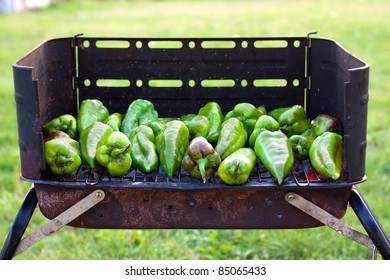 Green peppers baking on a barbecue outside on the grass