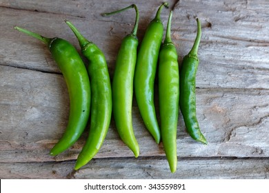 green peppers on wood background