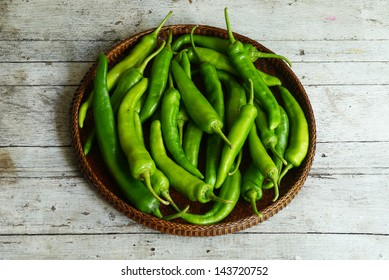 Green peppers in the threshing basket on wooden table